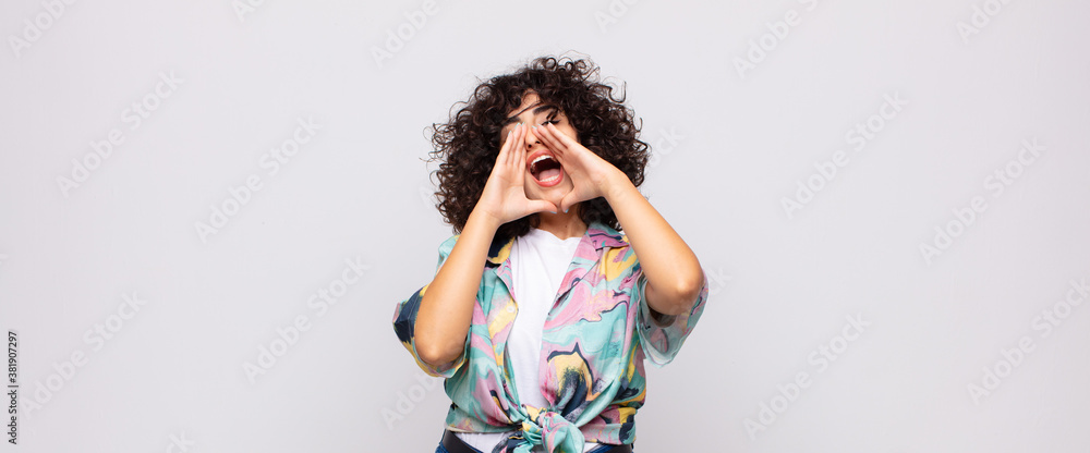 Fototapeta  feeling happy, excited and positive, giving a big shout out with hands next to mouth, calling out