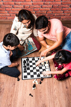Indian Happy Family Playing Board Games Like Chess, Ludo Or Snack And Ladder At Home In Quarantine