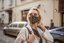 Outdoor Fashion, Lifestyle Portrait Of Elegant Woman Wearing Trendy Outfit With Protective Face Mask, Many Golden Chain Necklaces, Posing In Street Of European City. Copy, Empty Space For Text
