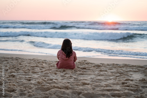 portrait girl in pink sweatshirt looking at the sea sitting on the sand with a l Wallpaper Mural