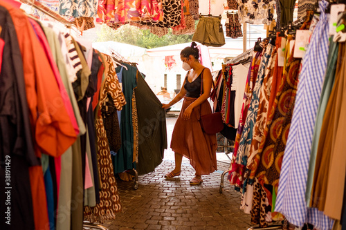 young woman shopping clothes with face mask after corona virus lockdown restrictions are lifted Canvas
