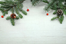 Christmas Decoration With Fir Branches, Pine Cones And Red Berries On Wooden Board, Top View With Place For Text