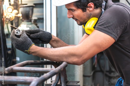 Caucasian man technician rasp steel pipe To get the right proportion, to people and worker concept Canvas Print