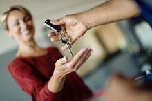 Close-up Of Woman Receiving Car Keys In Auto Repair Shop.