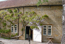 A Door Stands Open At The Way In To A Cotswold Stone Barn. Wisteria Grows Over The Door