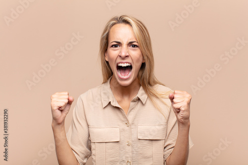 Fotografía shouting aggressively with an angry expression or with fists clenched celebrati