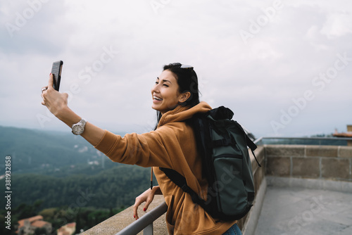 Платно Cheerful asian hipster girl recreating on vacations posing for selfie on destina