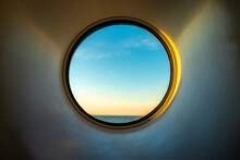 Sunset Ocean View Of Horizon Seen From Inside Of A Cruise Ship Cabin Through A Round Circular Window.