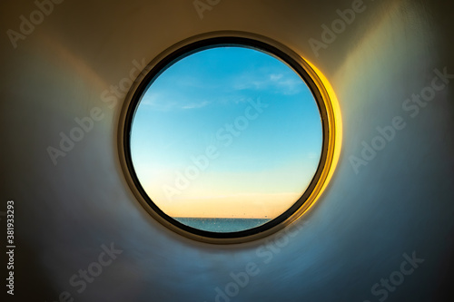 Cuadros en Lienzo Sunset ocean view of horizon seen from inside of a cruise ship cabin through a round circular window