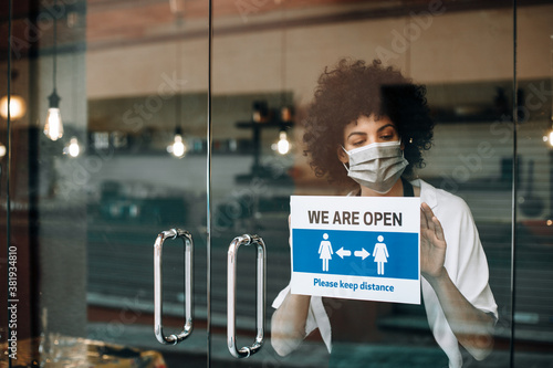 Obraz na plátně Coffee shop female owner with protective face mask, reopens after lockdown quarantine