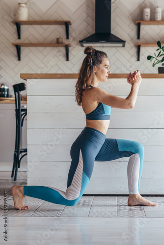 Fototapeta Fitness woman doing lunges exercise at home obraz