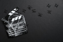 Halloween Scary Movie Concept. Flat Lay Composition With Clapper Board, Spider Web, Spiders On Black Background