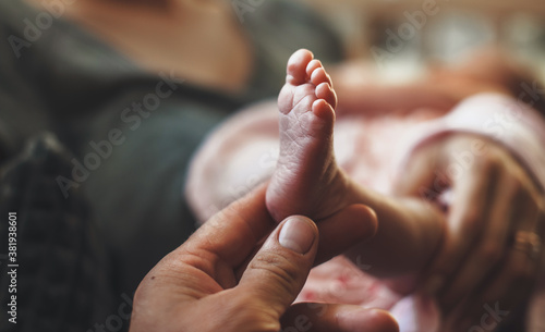 Obraz na plátně Newborn baby's leg held by his father and shown at camera after coming home