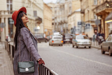 Outdoor Fashion, Lifestyle Portrait Of Elegant Woman Wearing Trendy Autumn Outfit: Hat, Checkered Coat, With Faux Crocodile Textured Shoulder Bag, Posing In Street Of European City. Copy, Empty Space