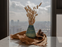 Dried Flowers In Beautiful Ceramic Blue Vase Handmade With Two Pine Cones On Marble Table Of Living Room And City View. Home Decor. Space For Text. Selective Focus.