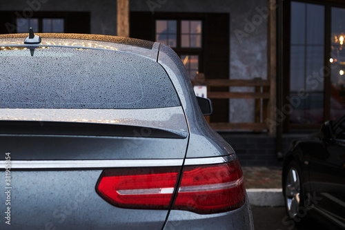 Back window of grey car parked on the street in autumn rainy day, rear view. Mock-up for sticker or decals © Alexey
