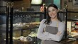 Proud young female baker working at her own bakery store. Happy beautiful woman wearing apron, smiling to the camera, standing at her bakery shop. 4k footage