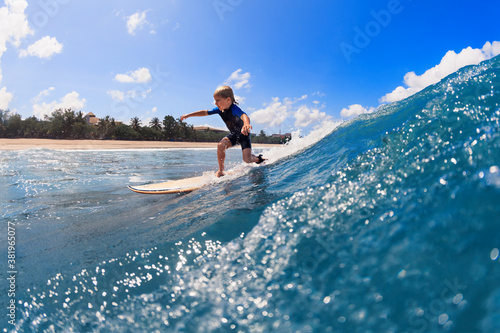 Foto Happy surf boy - young surfer learn to ride on surfboard with fun on sea waves