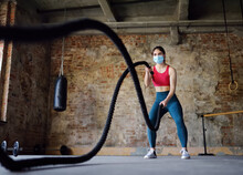 Young Woman Exercising With Battle Ropes At The Gym. Strong Female Athlete Doing Crossfit Workout With Battle Rope During Epidemic COVID-19