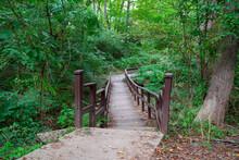 An Uneven Wooden Bridge Crossing A River In A Dense Green Forest