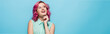 dreamy young woman with pink hair smiling and looking away isolated on blue, panoramic shot