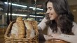Beautiful woman smelling freshly baked bread in a basket at bakery store. Attractive female customer enjoying smell of delicious bread, shopping at the bakehouse. 4k footage