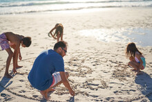 Family Drawing In Sand On Sunny Beach
