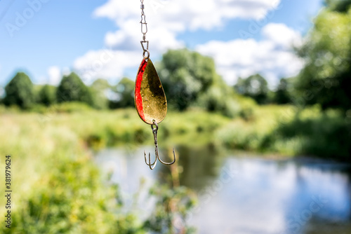 shine for fishing hangs/metal bait for fishing on the background of the river Poster Mural XXL