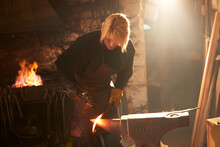 Female Blacksmith Forging Steel In Workshop