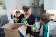 Mother And Sons Unloading Fresh Produce From Box In Kitchen