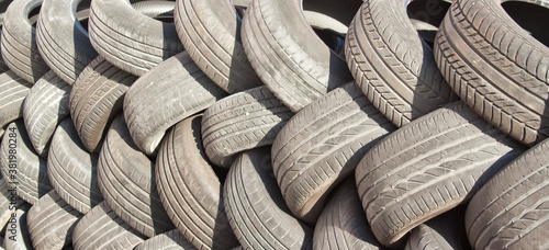 Background of old used car tires laid out in the shape of a pigtail Wallpaper Mural