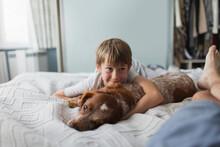 Cute Boy Cuddling With Dog On ...