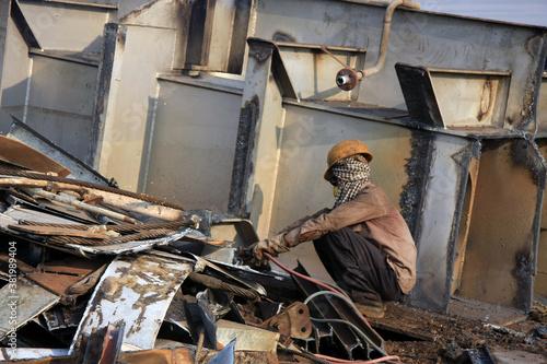 Naklejka premium Shipbreaking Yard in Darukhana, Mumbai, India – INS Vikrant dismantling with scrap metal & workers in background