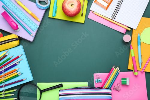 Different school supplies on chalkboard background