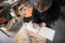 Male Carpenter Sketching Plans In Notebook In Workshop