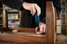 Close Up Male Carpenter Assembling Table With Screwdriver In Workshop
