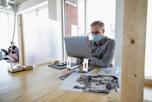 Designer In Face Mask Using Laptop In Socially Distanced Space