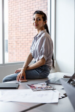 Portrait Of Young Creative Sitting On Desk In Workspace