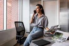 Young Creative Sitting On Desk Using Phone In Workspace