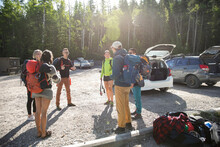 Young Friends Talking And Preparing To Camp In Sunny Parking Lot