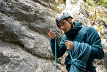 Young Male Rock Climber Examin...