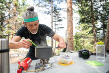 Man Cooking On Camping Stove A...