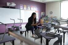 Teacher In Classroom Using Phone