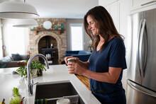 Smiling Woman Opening Jar At Kitchen Sink