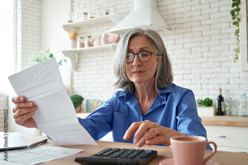 Fototapeta Senior mature business woman holding paper bill using calculator, old lady managing account finance, calculating money budget tax, planning banking loan debt pension payment sit at home kitchen table. obraz