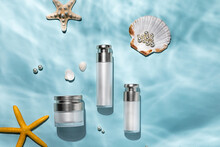 Top View Of Skincare Bottles On A Blue Water Surface With Seashells