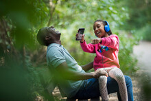 Happy Father And Daughter Laughing On Park Bench