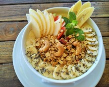 Healthy Fruit Smoothie Bowl Topped With Fresh Bananas, Asian Pear, Cashews, Chia Seeds, Granola And Mint