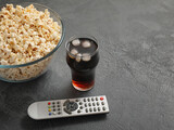 Tasty popcorn, cola and TV remote control on grey background