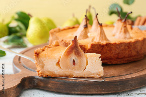 Board with tasty pear cake on table